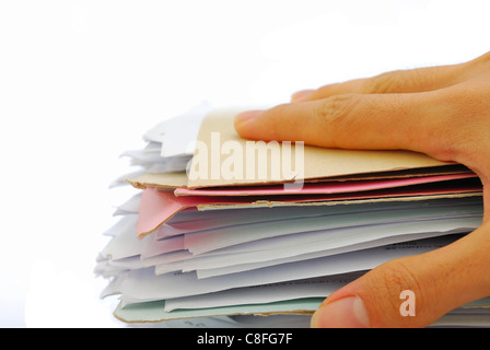 Hand on a stack of files full of documents signifying concepts such as work and stress, and work life and business - Stock Photo