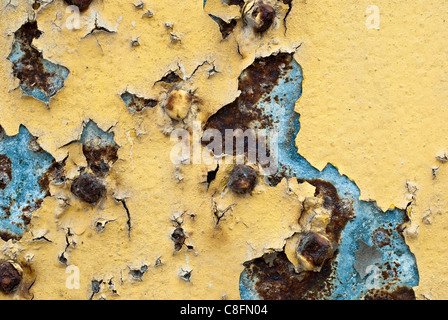 Antique metal door with rust and peeling layers of old color, yellow, cyan and rusty brown. Closeup. iron rusting - Stock Photo