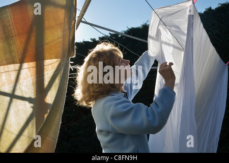 Woman drying clothes, New Zealand - Stock Photo