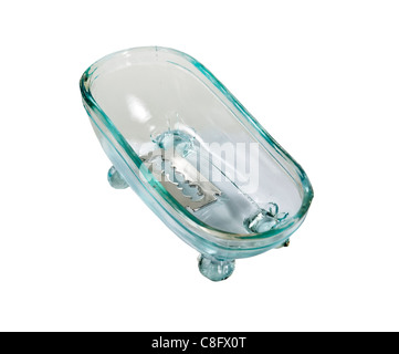 Antique glass claw footed bathtub for bathing with a silver razor blade inside - path included - Stock Photo
