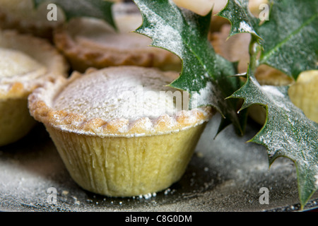 Close up of mince pies dusted with icing sugar on black plate with holly sprigs - Stock Photo