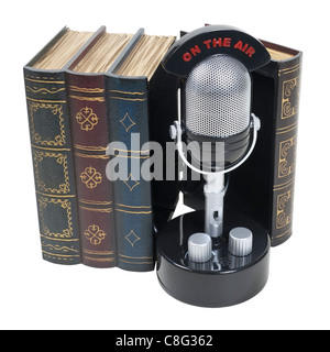 Story broadcasts shown by a retro pill audio microphone with an on the air banner inside a set of books - path included - Stock Photo