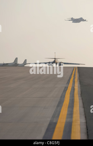 While a C-17 Globemaster III flies overhead, a B1-B Lancer taxis on a runway ready to take-off on a combat mission - Stock Photo