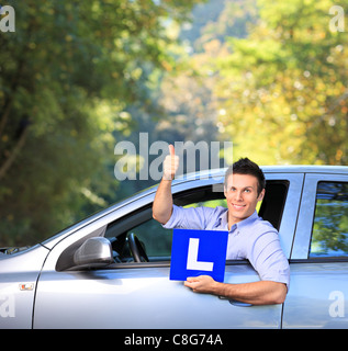 Happy male in his car holding a L sign and giving thumb up - Stock Photo