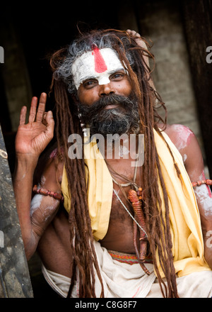 A Sadhu poses for the camera at the holy Hindu temple complex of Pashupatinath on the banks of the Bagmati River, - Stock Photo