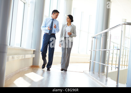 Confident business partners walking down in office building and discussing work - Stock Photo
