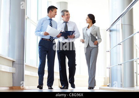 Confident business partners walking down and discussing work - Stock Photo