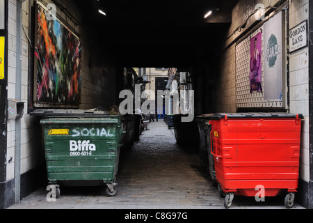 Refuse bins line a back street lane in Glasgow - Stock Photo