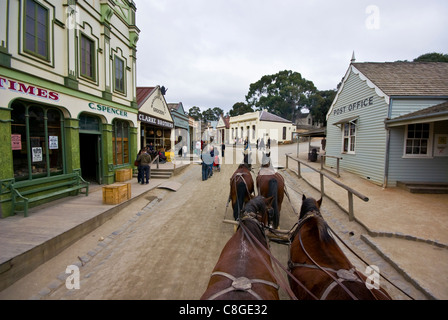 A team of Clydesdale horses pull a stagecoach in a gold mining town. - Stock Photo