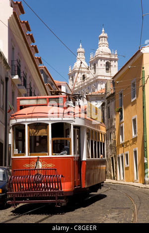 A tram runs along the tourist friendly Number 28 route in Alfama, Lisbon, Portugal - Stock Photo