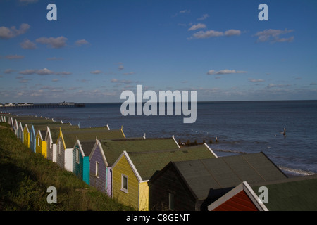 Colourful beach huts look out over the sea under a bright blue sky at Southwold in Suffolk - Stock Photo