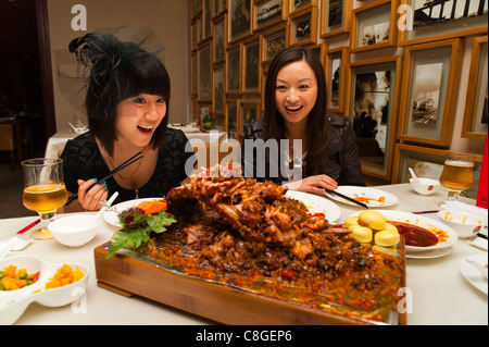 Tourists surprised by the food in a Sichuan cuisine restaurant, Haiyongxiang District, Shanghai, China - Stock Photo