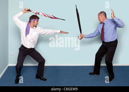 Photo of two businessmen having a sword fight using umbrellas, good image to convey conflict, rivalry or disagreement. - Stock Photo