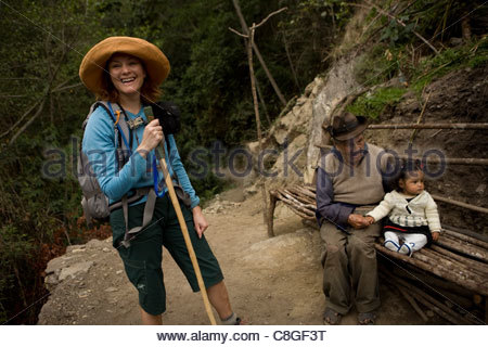 A hiker pauses to meet a 100 year old man and his great granddaughter. - Stock Photo