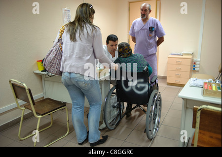 Doctor talking to patient in wheelchair - Stock Photo