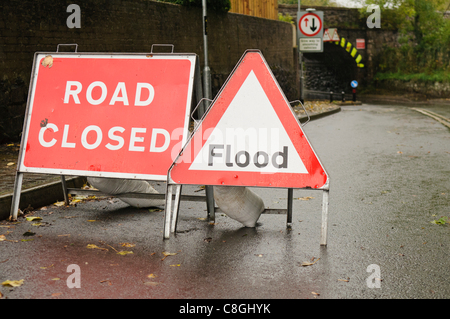 Road closed and flood signs on the approach to a flooded road. - Stock Photo