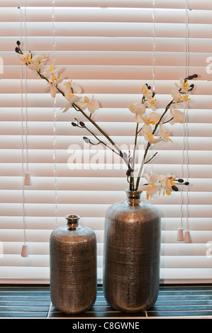 Bottle vases with fake flowers on a window sill - Stock Photo