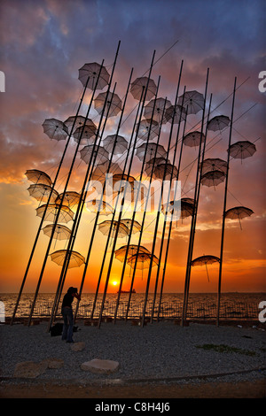 Greece, Thessaloniki. A lady photographer taking photos of a  structure, called 'The Umbrellas' by George Zoggolopoulos. - Stock Photo