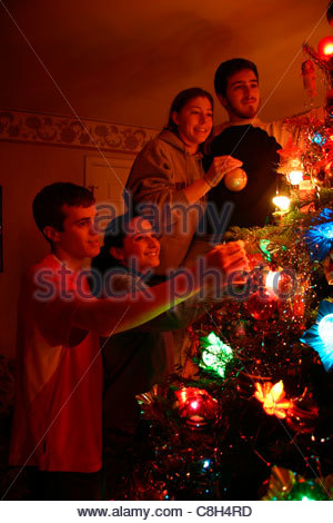 Four young people decorate a traditional Christmas tree. - Stock Photo