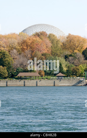 The Montreal Biosphere visible through fall colors at Jean Drapeau Parc on Ile Sainte-Helene in Montreal, Canada - Stock Photo