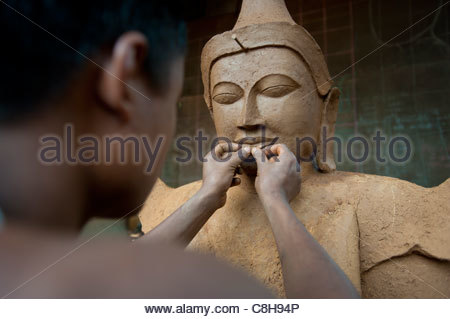 A man sculps a Buddha from clay which will eventually be bronzed. - Stock Photo