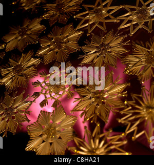 full frame studio photography showing a christmas background with red fabrics and gold toned straw stars - Stock Photo