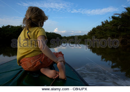 A girl rides on the bow of a boat on a river in Borneo. - Stock Photo
