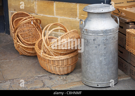 Wicker baskets and milk churn outside shop in the Cotswold Cheese Company, Cotswolds in July - Stock Photo