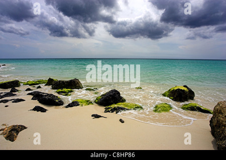 Looking out to sea over rocks on Druif beach in Aruba , the Caribbean sea stretching to the distance, a cloudy sky - Stock Photo