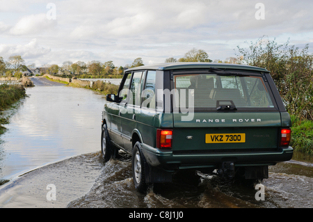 Man drives Range Rover through flooded rural road in Northern Ireland on Tuesday, 25th October, 2011. - Stock Photo