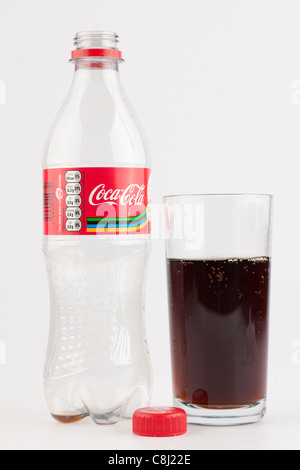 Empty plastic bottle of Coca Cola and a partly filled plain glass - Stock Photo