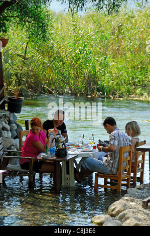AKYAKA, TURKEY. A Turkish family eating at a restaurant by (or, more specifically, in) the Azmak river. 2011. - Stock Photo