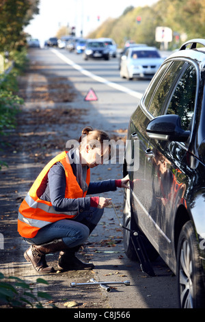 Car breakdown, flat tire. Woman changes a tire of a car on a highway, wearing a high visibility vest. - Stock Photo