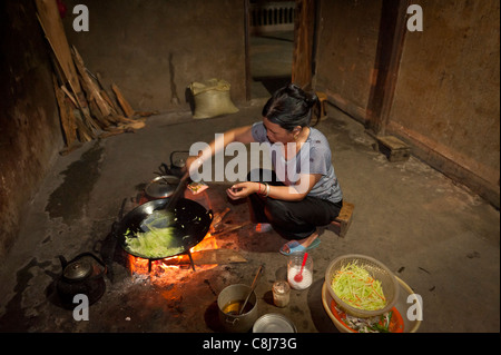 Vietnamese woman cooking on an indoor fire pit - Stock Photo