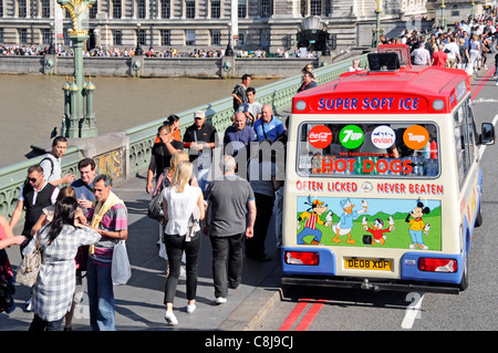 Ice Cream and Hot Dog van parked in road beside pavement busy with tourists on Westminster Bridge London England - Stock Photo