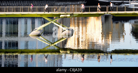 People walking across North Dock footbridge and reflection on West India Quay at Canary Wharf Isle of Dogs Tower - Stock Photo