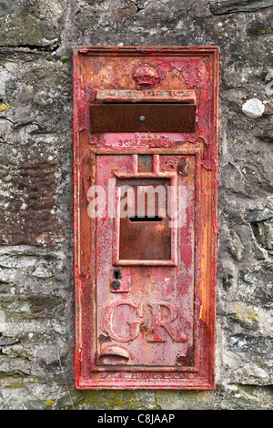 Red 'Royal Mail' 'letter box' in old [stone wall], 'Lake District', Cumbria, England, UK - Stock Photo