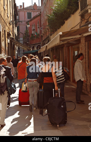 Woman Tourists with bags and cases in a small street, Venice Italy - Stock Photo