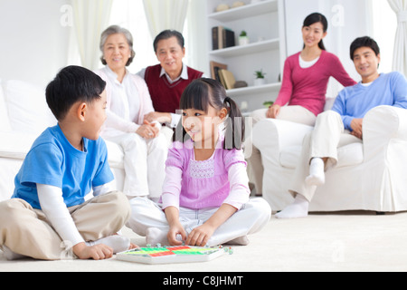 Chinese children playing with toys on the floor with grandparents and parents behind them - Stock Photo