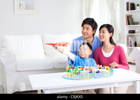 Young Chinese boy with parents and world map with flags and paper airplane - Stock Photo