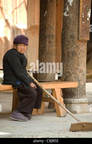 Granny resting while drying rice grains on a mat in warm sun - Stock Photo