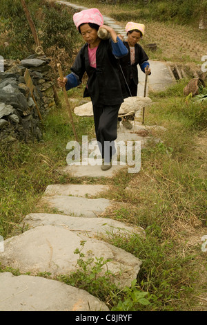 Carrying a heavy rock to a building site in a village in China Living in hills of China surrounded by rice fields. - Stock Photo