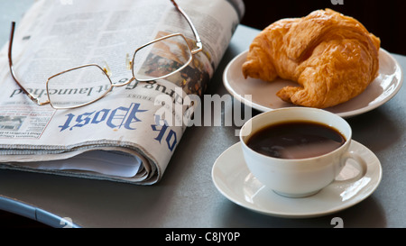 Fresh-baked croissant, Hot coffee and newspaper. reading glasses. Focus on cup. - Stock Photo