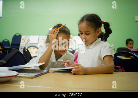 Second and third graders do homework during an after school program in New York - Stock Photo
