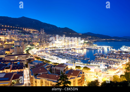 Dusk view of Port Hercule and the city and Principality of Monaco on the French Riviera along the Mediterranean - Stock Photo