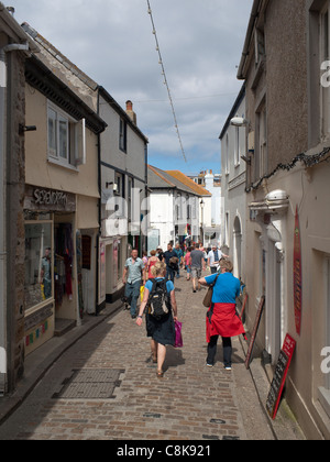 Fore Street in St. Ives, a narrow cobblestone street with shops on both sides. - Stock Photo