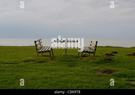 A picnic bench on a blustery day in Clarach near Aberystwyth. - Stock Photo