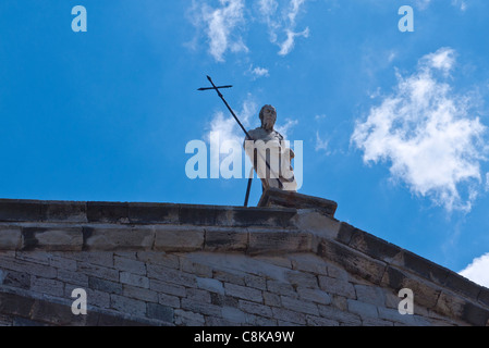 A rooftop statue of Saint John the Baptist on a church in Chianciano Terme, Umbria, Italy. - Stock Photo