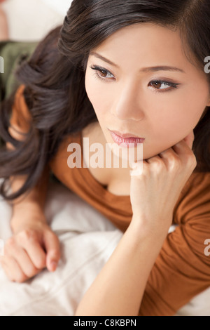 A beautiful young Chinese Asian Oriental woman relaxing and thoughtful - Stock Photo