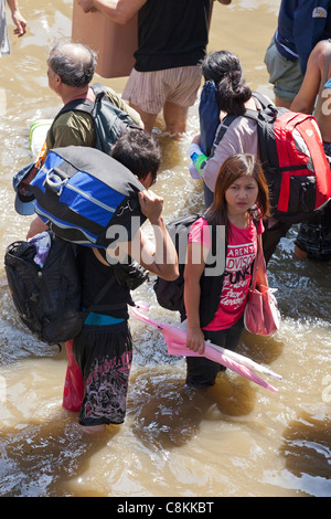 People wading through flood water in Bangkok city centre, Thailand - Stock Photo